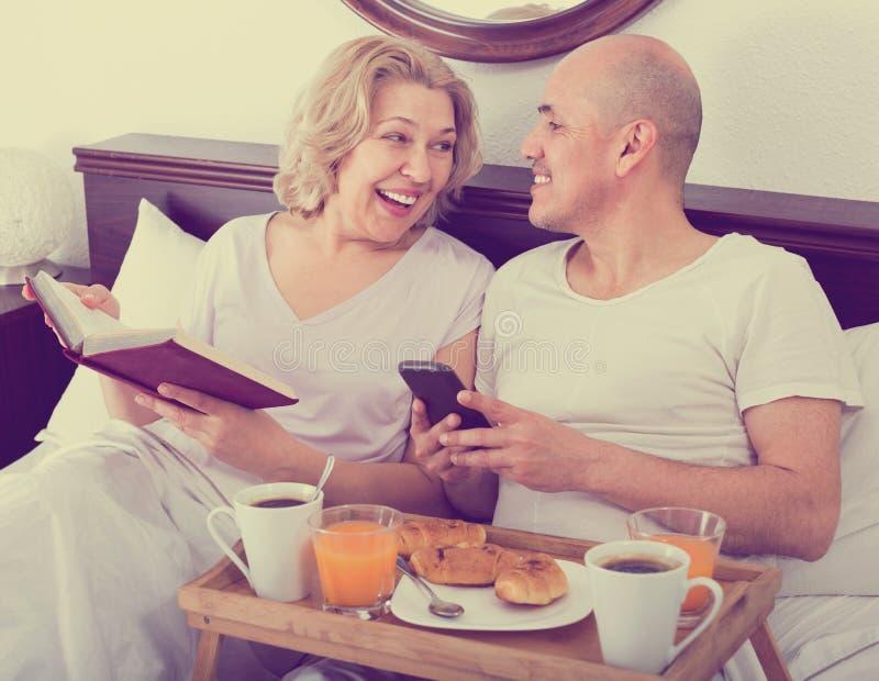 Vrolijk positief die rijpe volwassenen glimlachen die met ontbijt stellen royalty-vrije stock afbeelding