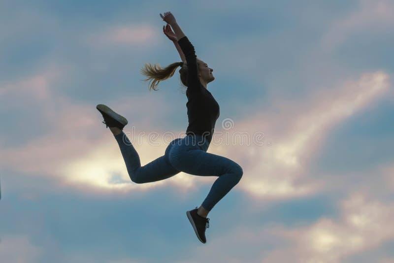 Vrolijk Positief Meisje die in de Wolken van de Lucht Openluchtochtend, de Training van de de Zonsopgangochtend van Atletenwoman  stock fotografie