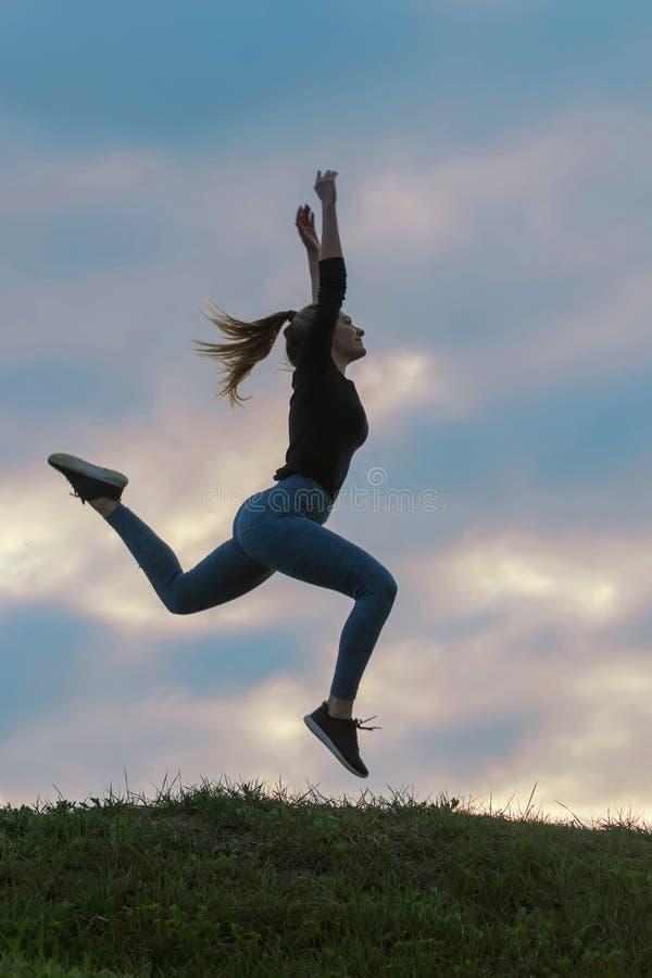 Vrolijk Positief Meisje die in de Wolken van de Lucht Openluchtochtend, de Training van de de Zonsopgangochtend van Atletenwoman  stock foto's