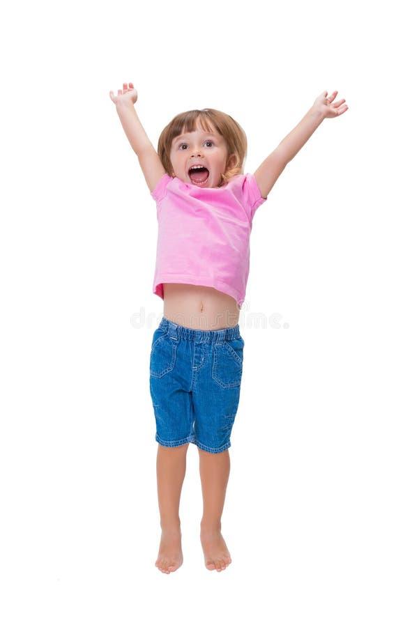 Vrolijk positief meisje 3 jaar het oude die gelukkig springen omhoog en het gillen toejuichingen op witte achtergrond worden geïs stock afbeeldingen