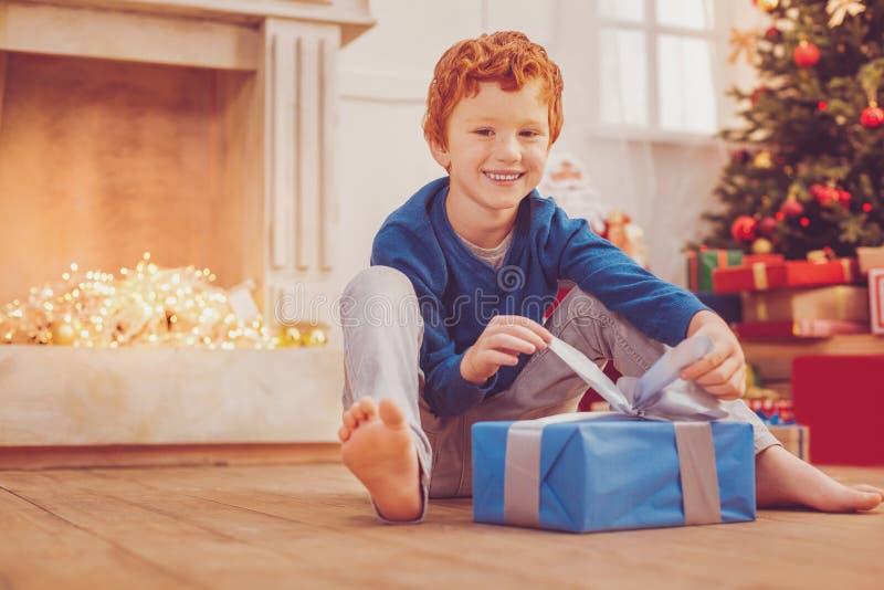 Vrolijk preteen jongen die zijn aanwezige Kerstmis openen stock afbeeldingen