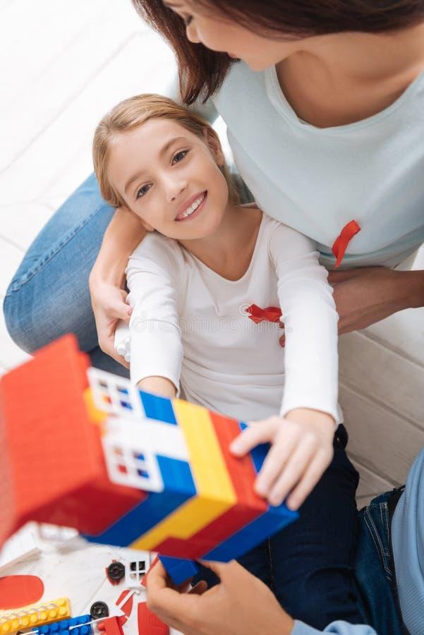 Vrolijk prettig meisje die het stuk speelgoed huis tonen royalty-vrije stock foto