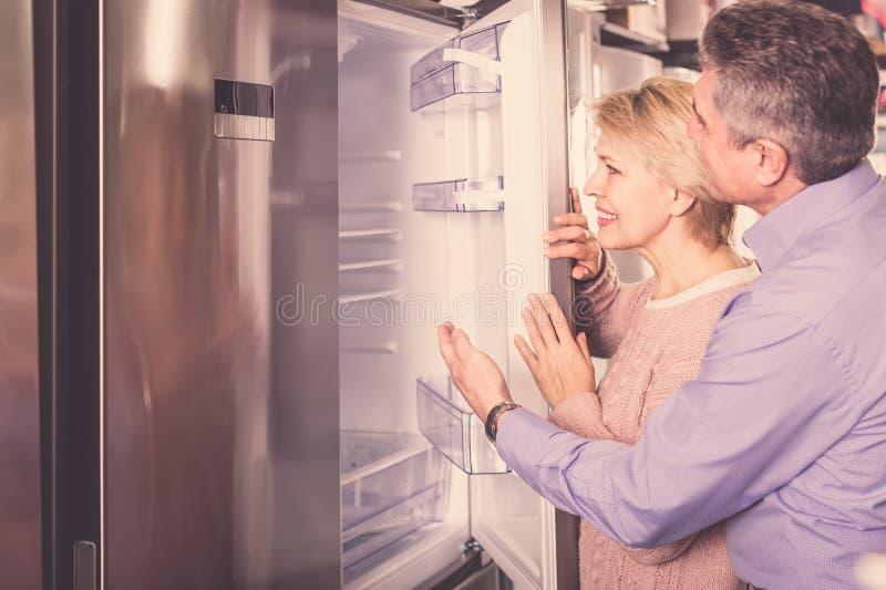 Vrolijk rijp echtpaar in winkel van huishoudapparaten a royalty-vrije stock afbeeldingen