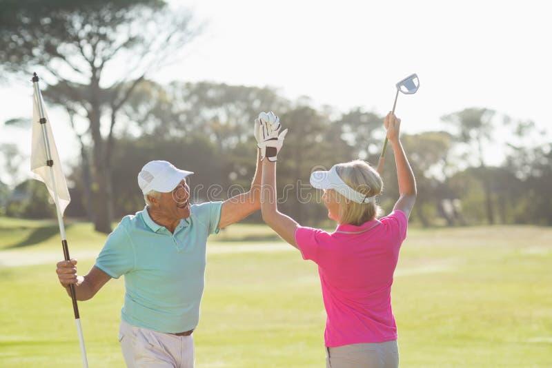 Vrolijk rijp golfspelerpaar die hoogte vijf geven royalty-vrije stock afbeelding