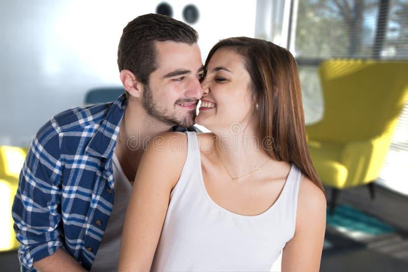 Vrolijk romantisch paar van minnaars die in huiswoonkamer knuffelen in het huis van de jaren '50stijl stock afbeelding