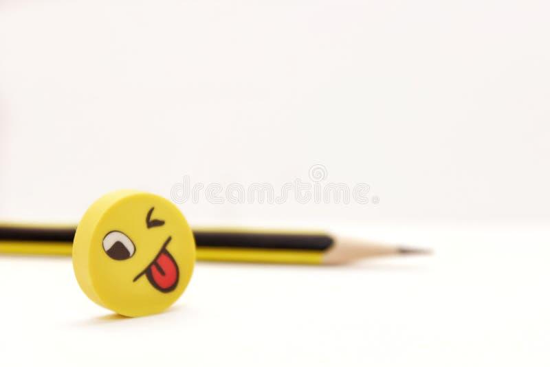 Vrolijk schadelijk geel gezicht en potlood op een lichte achtergrond stock afbeelding