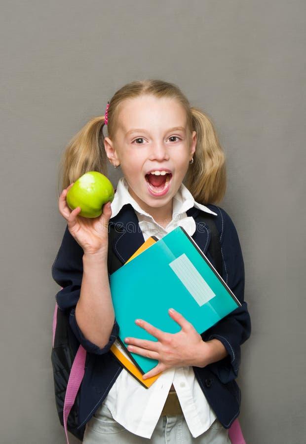 Vrolijk schoolmeisje met voorbeeldenboeken en appel. royalty-vrije stock afbeelding