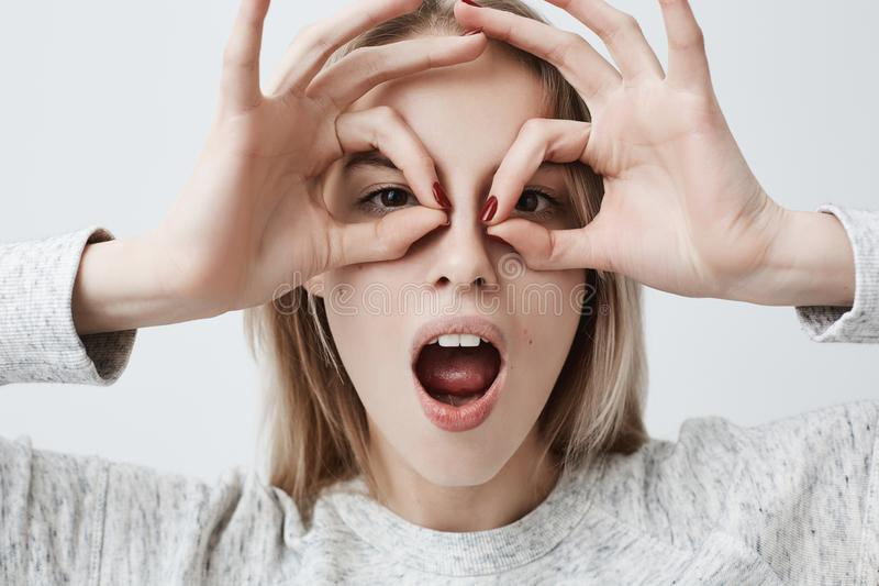 Vrolijk speels jong wijfje met blondehaar die O.k. gebaren met beide handen tonen, die bril beweren te dragen stock foto