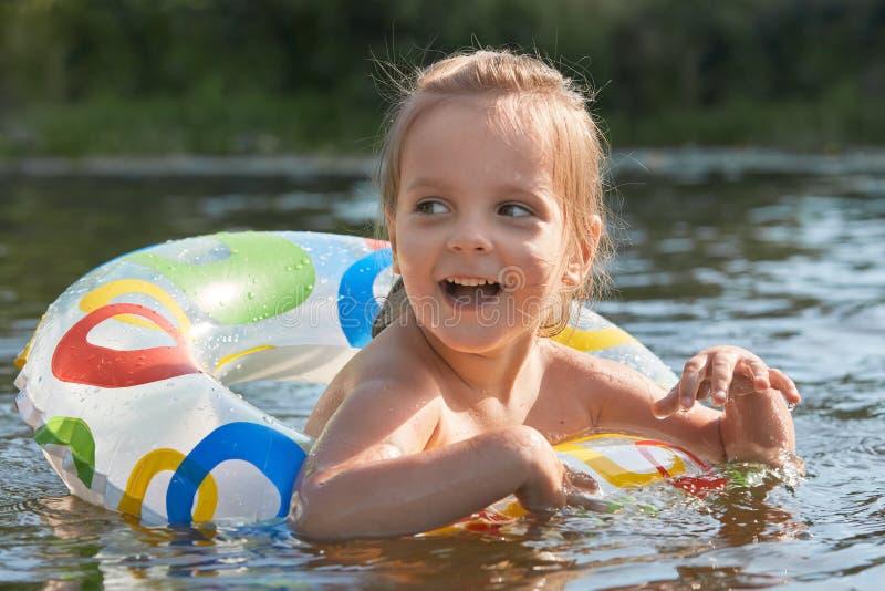 Vrolijk speels littlmeisje die met hulp die van zwemmende cirkel zwemmen, haar mond wijd met opwinding openen, die opzij eruit zi royalty-vrije stock afbeeldingen