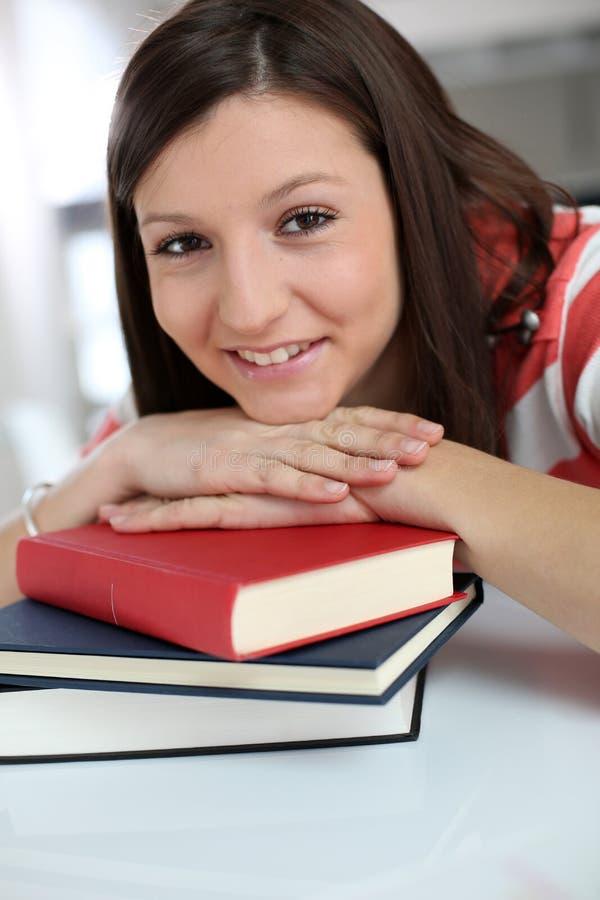 Vrolijk studentenmeisje die op boeken leunen stock foto's