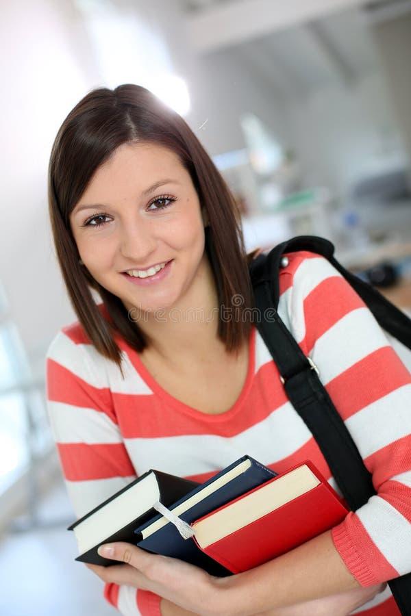 Vrolijk studentenmeisje in klasse met boeken stock afbeeldingen