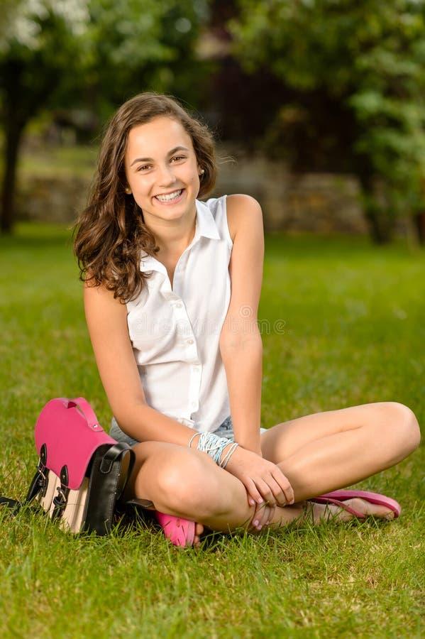 Vrolijk studentenmeisje met het gras van de aktentaszitting stock fotografie