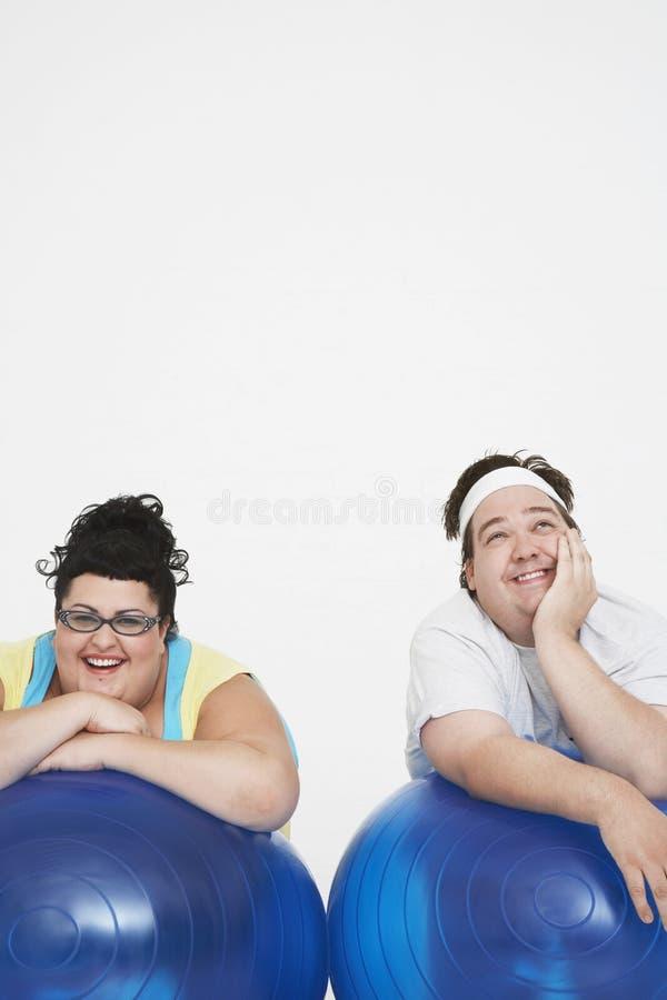Vrolijk Te zwaar Paar die op Oefeningsballen rusten royalty-vrije stock afbeeldingen