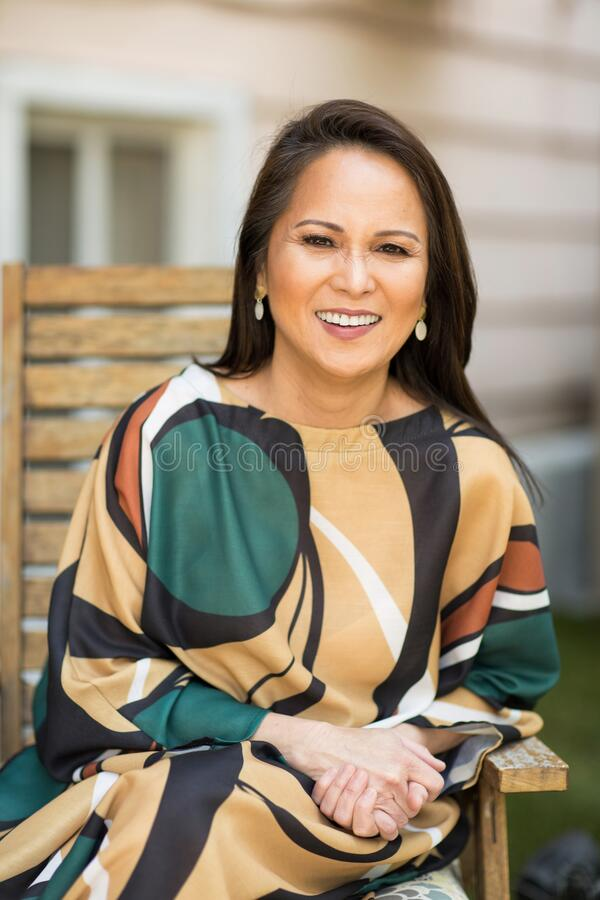 Vrolijk volwassen Aziatische vrouw lachen en glimlachen stock foto's