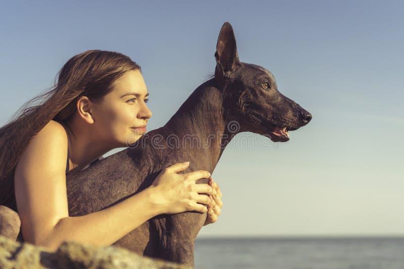 Vrolijk vrij jong meisje die en haar hondxoloitzcuintli zitten koesteren bij de blauwe hemel bij zonsondergang stock foto's