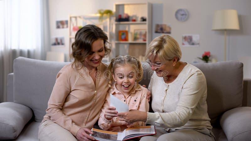 Vrolijk vrouwelijk familie het bekijken fotoalbum en het glimlachen, goed geheugen, pret stock fotografie