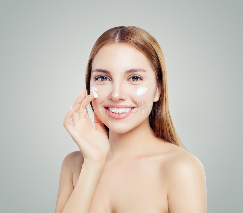 Vrolijk vrouwelijk model die anti-veroudert room op haar gezicht toepassen Huidzorg, schoonheid en gezichtsbehandelingsconcept royalty-vrije stock afbeelding