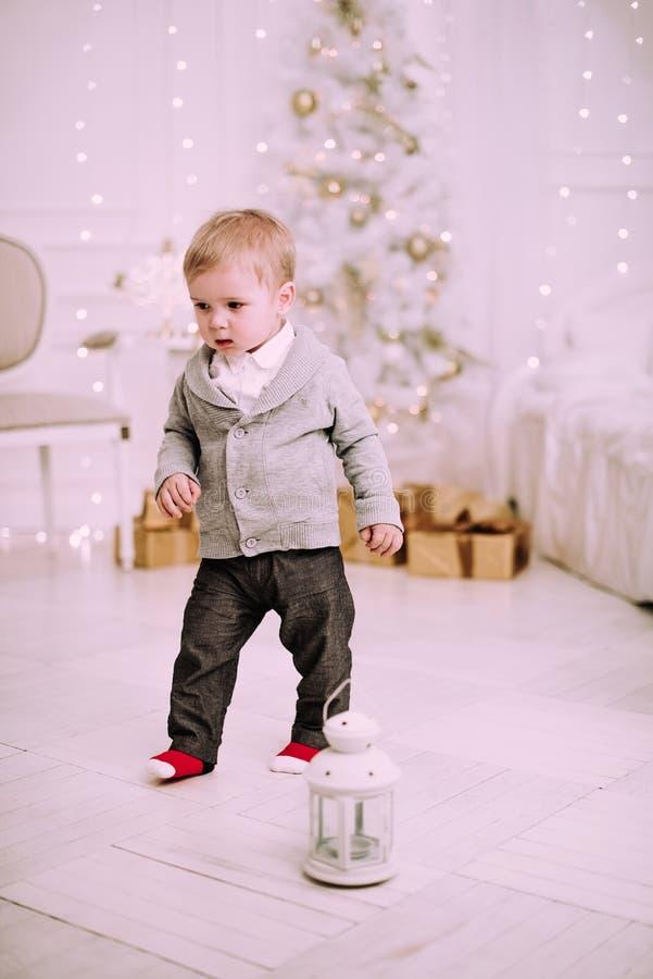 Vrolijk weinig babyjongen die dichtbij Kerstboom, gouden en beige pastelkleur c spelen stock afbeeldingen