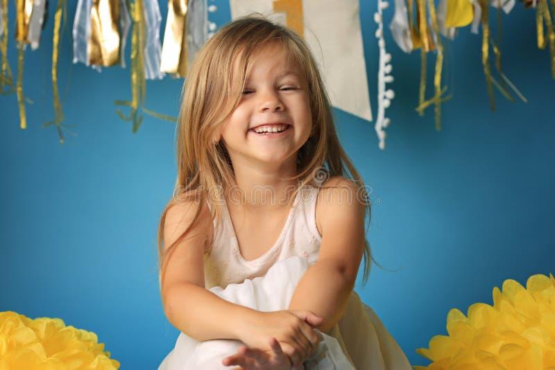 Vrolijk weinig blond meisje op blauwe achtergrond stock afbeelding