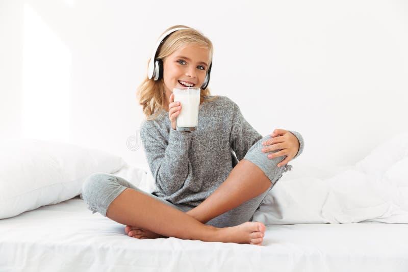 Vrolijk weinig blondemeisje die in grijze pyjama's glas van mil houden royalty-vrije stock afbeelding