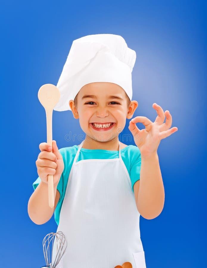 Vrolijk weinig chef-kok die goede smaak tonen stock fotografie