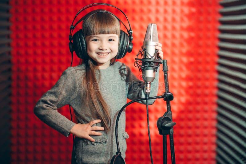 Vrolijk weinig jong geitje met lang bruin haar die haar album registreren stock foto