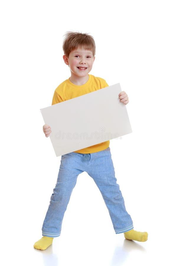 Vrolijk weinig jongen in een gele t-shirt en jeans stock foto