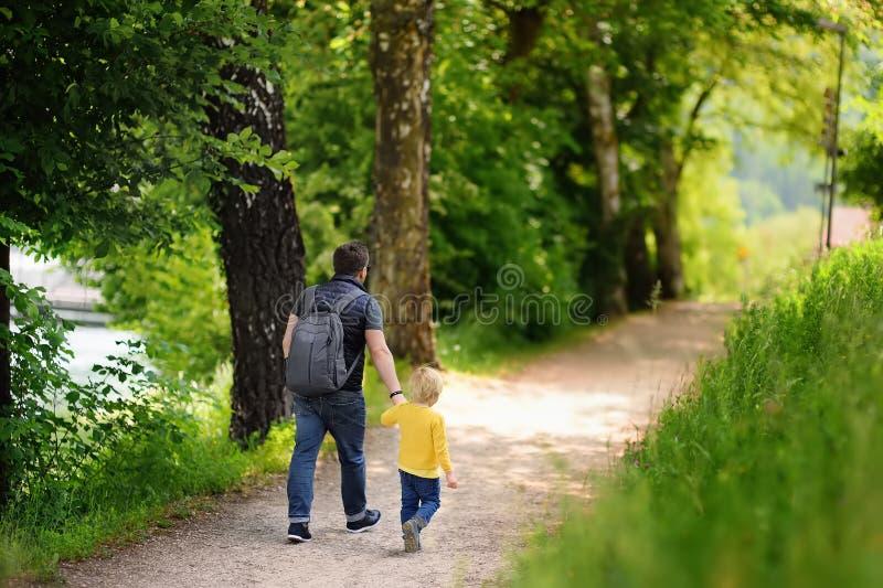 Vrolijk weinig jongen en zijn vader die van warme de zomerdag genieten stock foto's