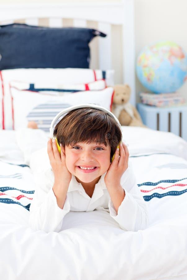 Vrolijk weinig jongen het luisteren muziek op zijn bed stock foto