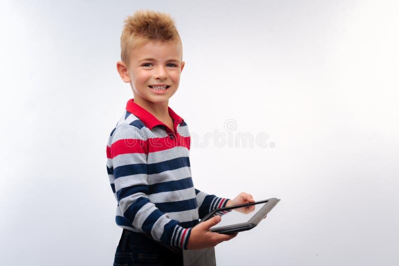 Vrolijk weinig jongen het stellen met een tablet stock foto's