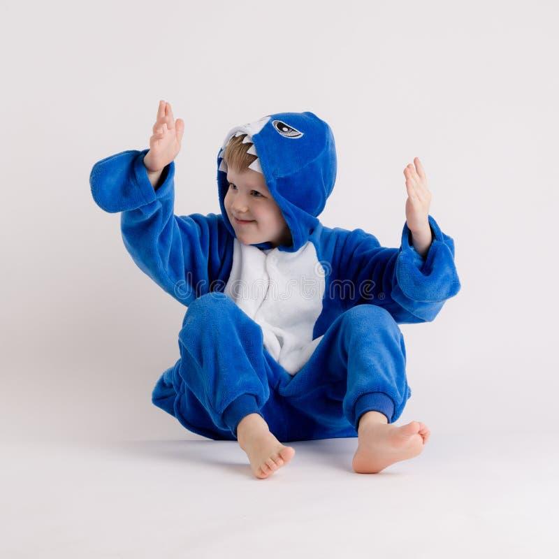 Vrolijk weinig jongen het stellen op een witte achtergrond in pyjama's, blauw haaikostuum stock fotografie