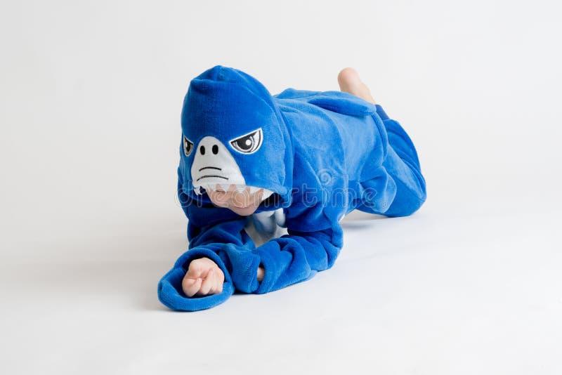 Vrolijk weinig jongen het stellen op een witte achtergrond in pyjama's, blauw haaikostuum stock foto