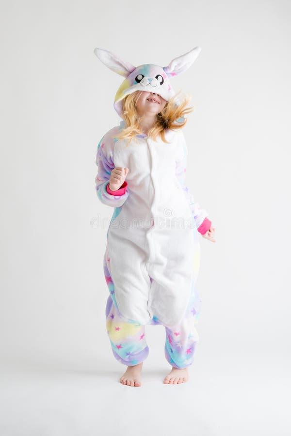 Vrolijk weinig jongen het stellen op een witte achtergrond in pyjama's, blauw haaikostuum stock foto's
