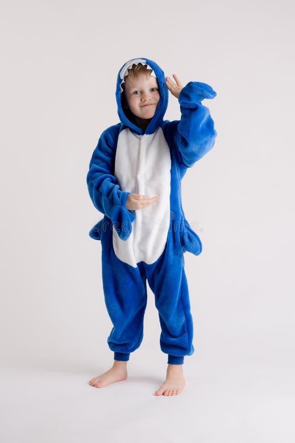 Vrolijk weinig jongen het stellen op een witte achtergrond in pyjama's, blauw haaikostuum royalty-vrije stock foto