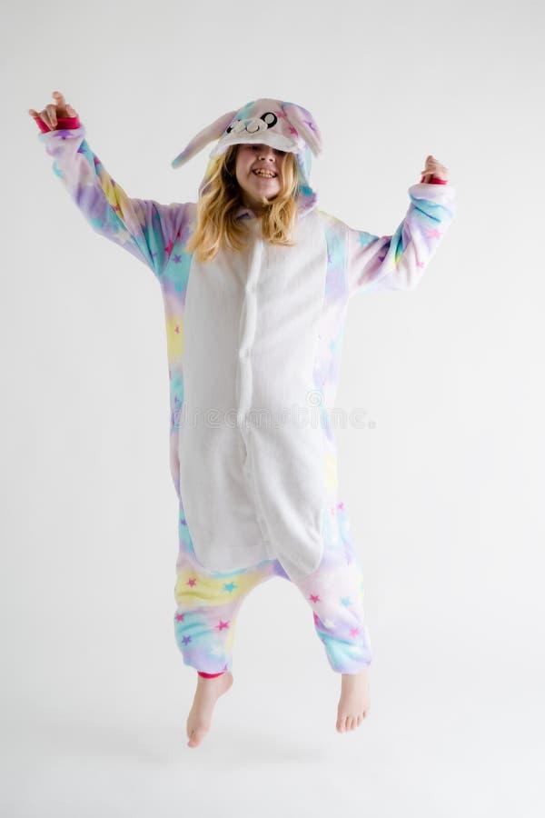 Vrolijk weinig jongen het stellen op een witte achtergrond in pyjama's, blauw haaikostuum stock afbeelding