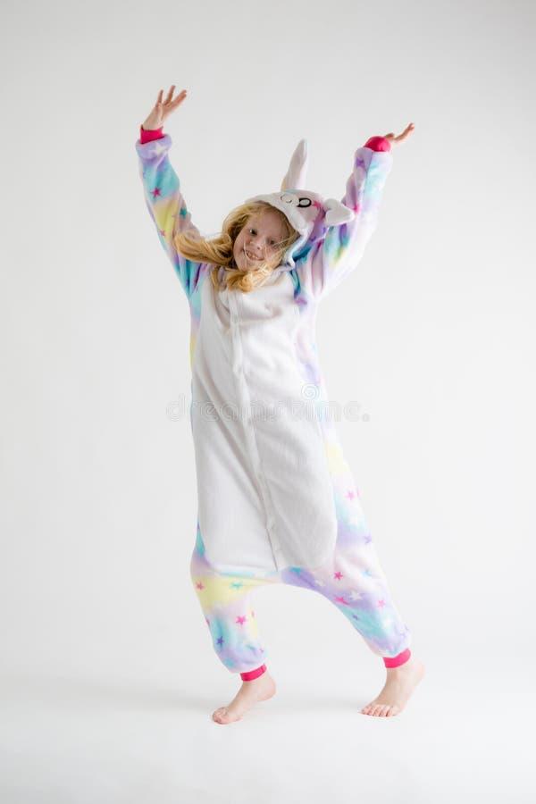 Vrolijk weinig jongen het stellen op een witte achtergrond in pyjama's, blauw haaikostuum royalty-vrije stock afbeelding