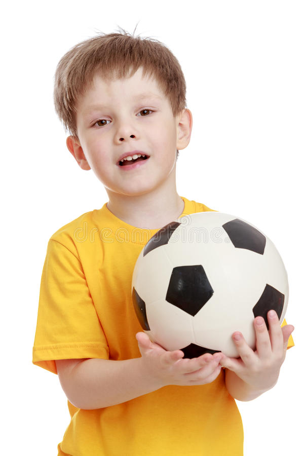 Vrolijk weinig jongen met een voetbal in zijn handen stock afbeelding