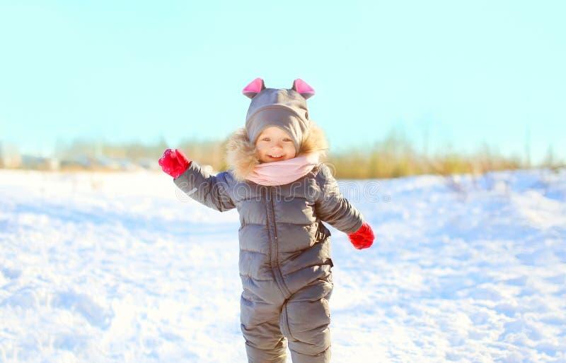 Vrolijk weinig kind die op sneeuw in de winter spelen stock afbeeldingen