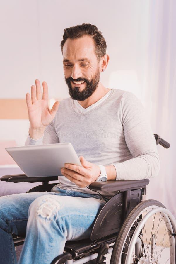 Vrolijk wheelchaired de mens uisng een tablet voor mededeling stock afbeelding