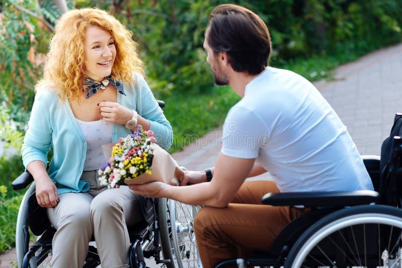 Vrolijk wheelchaired vrouw die een bos van bloemen krijgen royalty-vrije stock fotografie