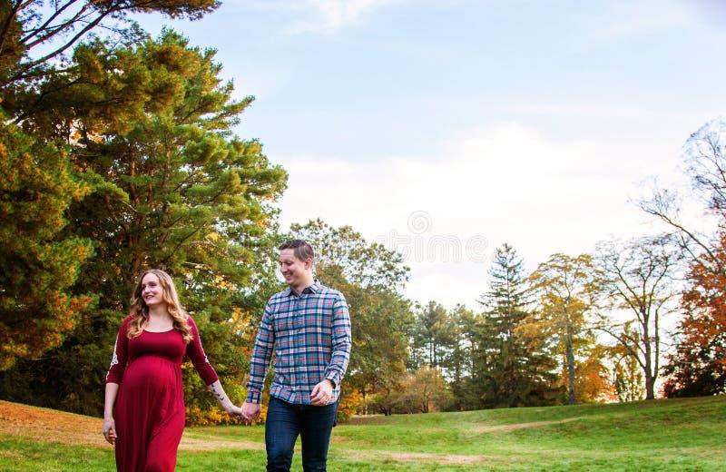 Vrolijk zwanger koppel met handen buiten het najaar royalty-vrije stock afbeeldingen