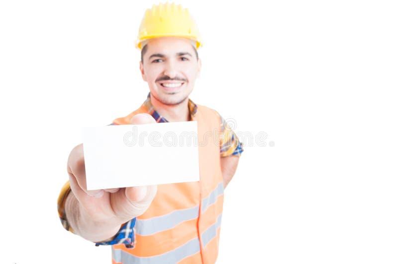 Vrolijke aannemer die lege bezoekkaart in close-up tonen stock foto