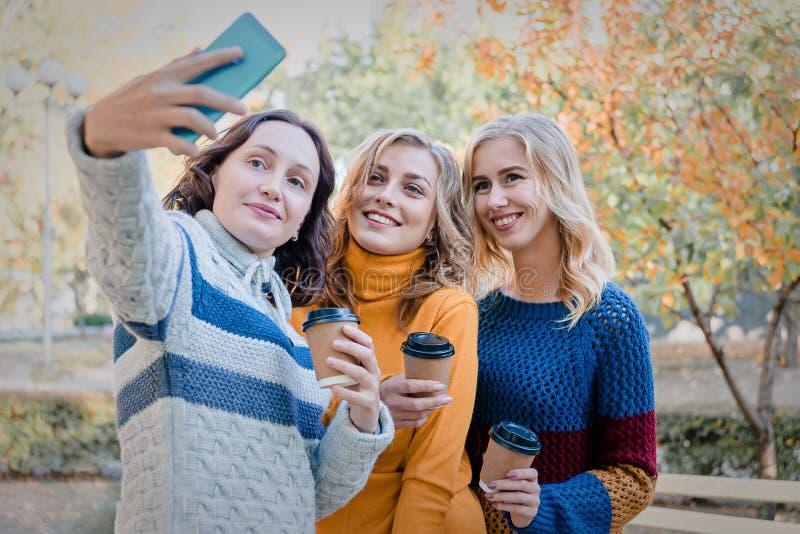 Vrolijke aantrekkelijke drie jonge pret hebben samen buiten en vrouwen beste vrienden die selfie maken stock afbeeldingen