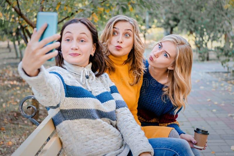 Vrolijke aantrekkelijke drie jonge pret hebben samen buiten en vrouwen beste vrienden die selfie maken royalty-vrije stock fotografie