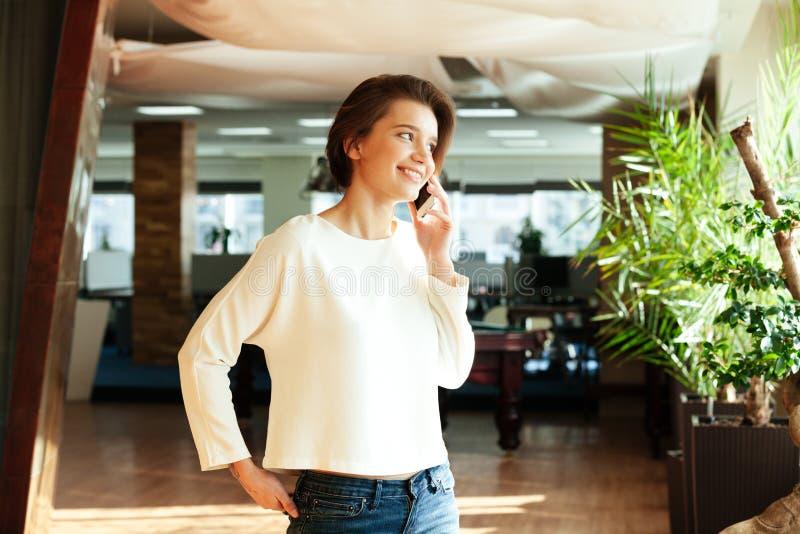Vrolijke aantrekkelijke jonge vrouw die op mobiele telefoon in bureau spreken royalty-vrije stock foto's