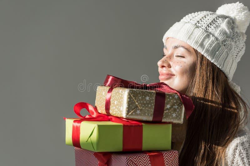 vrolijke aantrekkelijke vrouw in de modieuze van de de wintersweater en sjaal geïsoleerde dozen van de holdingsgift stock foto's