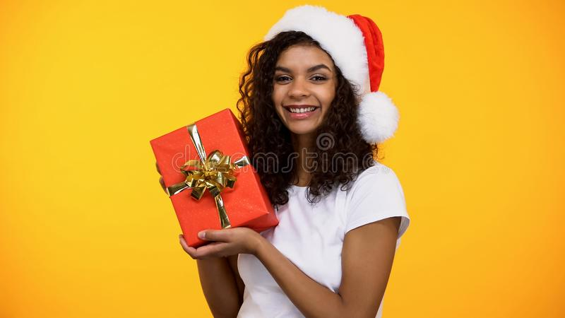 Vrolijke aantrekkelijke vrouw die in de hoed van de Kerstman rode gift doos en het glimlachen houden stock fotografie