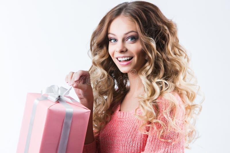 Vrolijke aantrekkelijke vrouw met het openen van gift op wit stock afbeelding