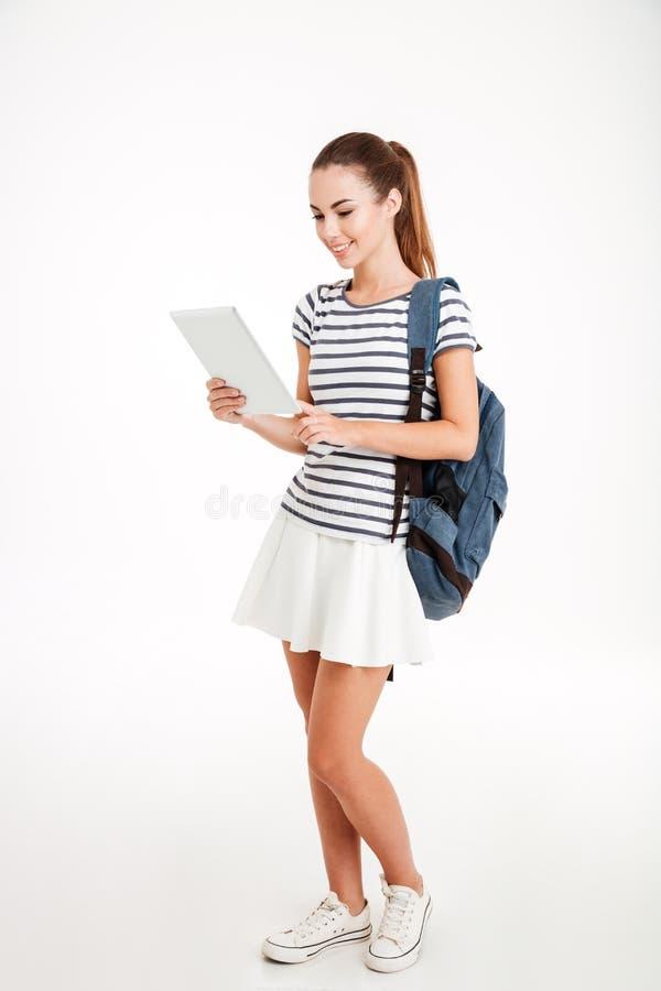 Vrolijke aantrekkelijke vrouw met rugzak die tabletcomputer met behulp van stock afbeeldingen