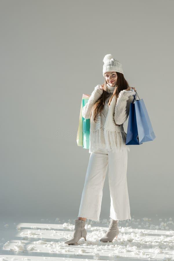 vrolijke aantrekkelijke vrouw in modieuze de wintersweater en sjaal die zich met het winkelen zakken bevinden stock afbeelding